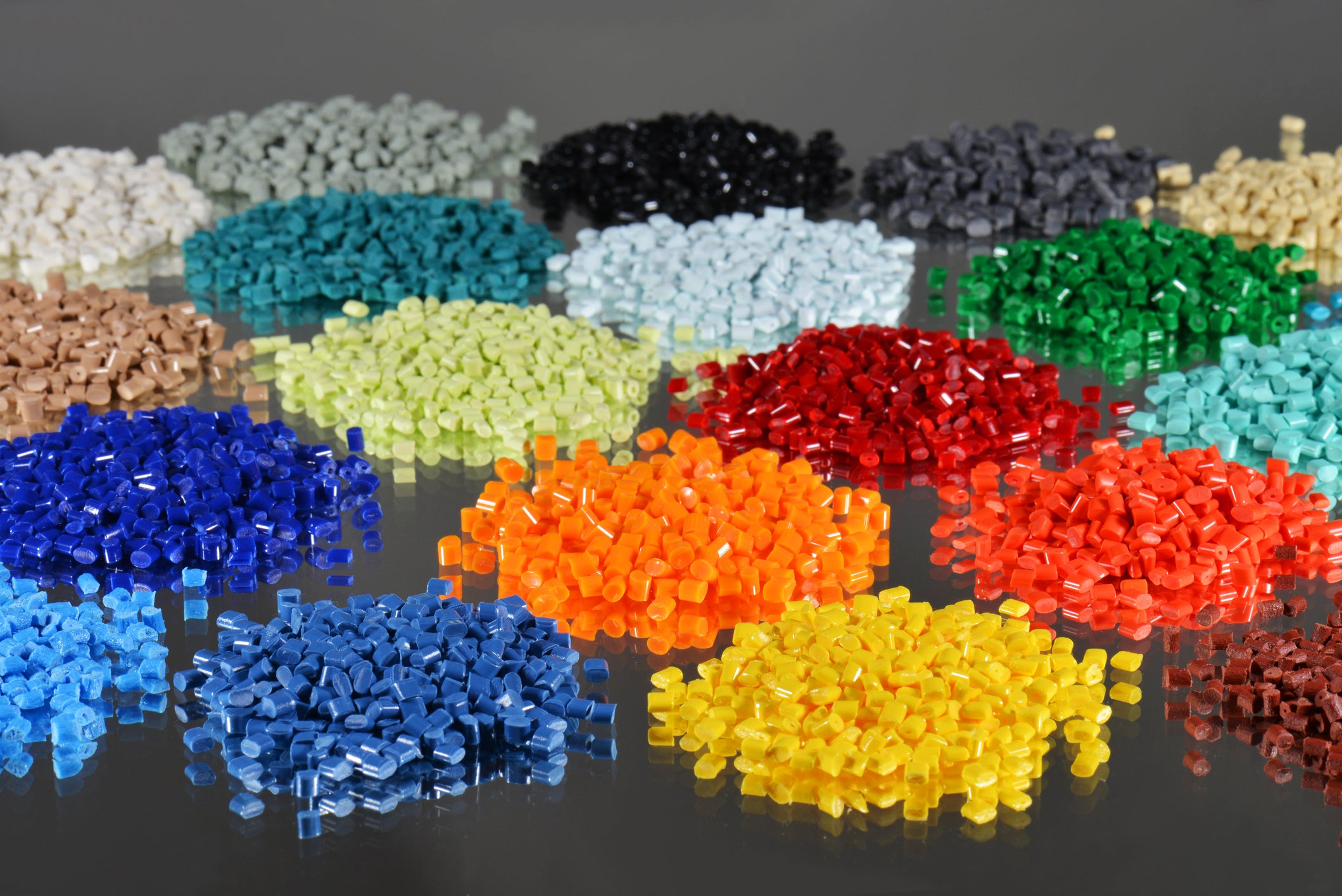 Several dyed polymer resins from the plastic industry on a mirror.