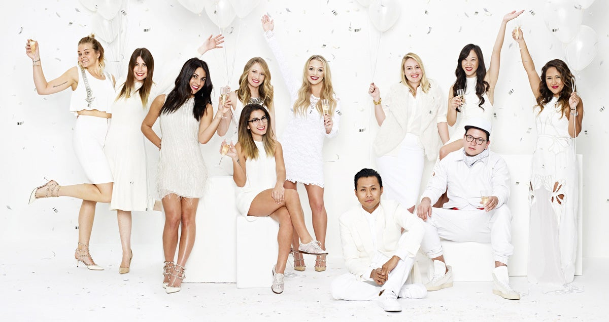 A group of men and women dressed in white posing for a picture in a celebratory manner