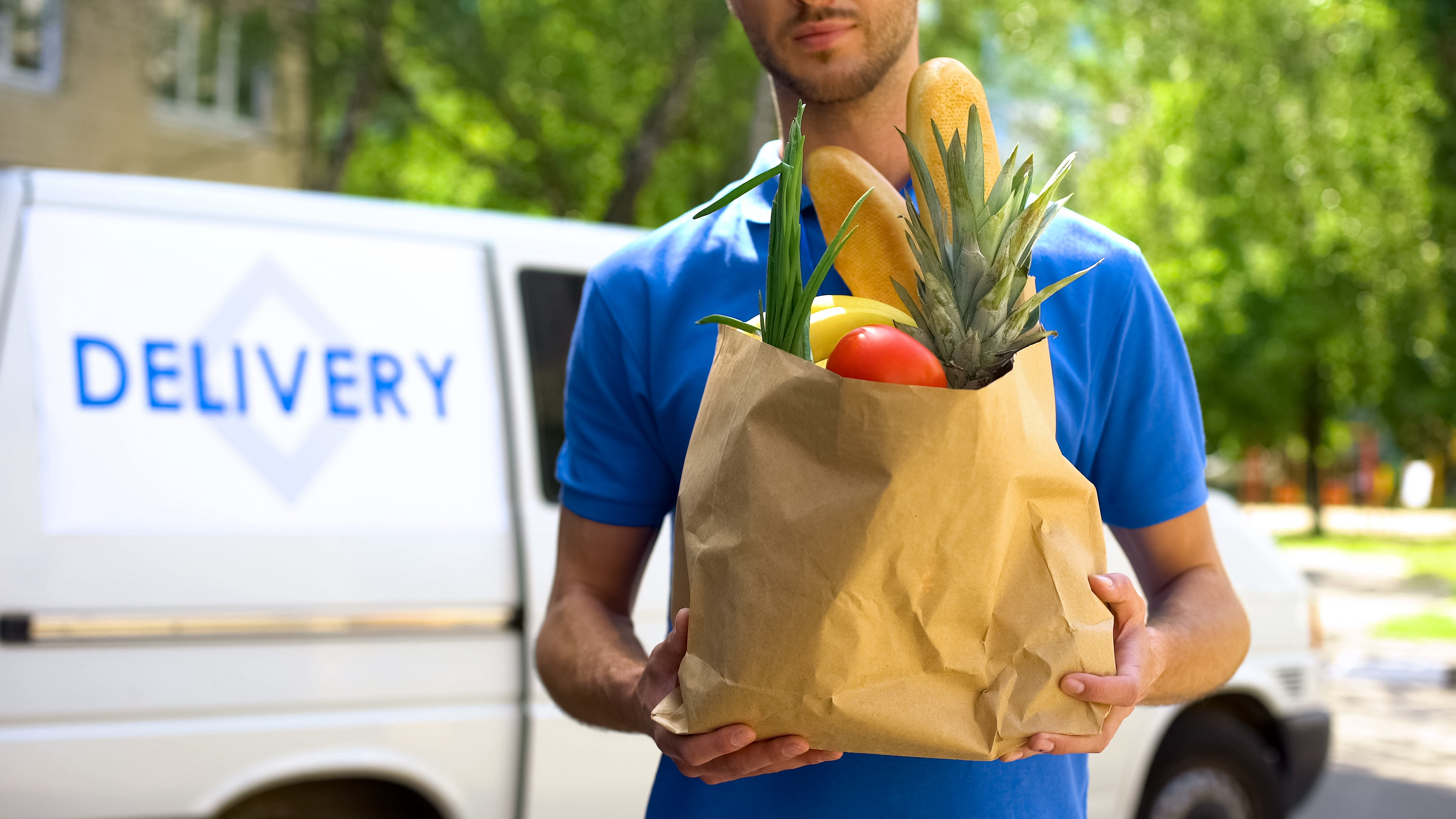 A delivery person brings groceries to a customer's door.