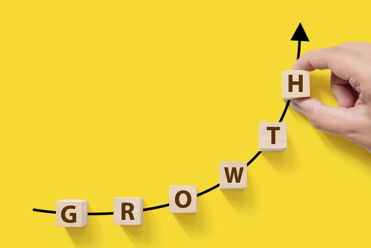 A hand placing blocks spelling the word growth onto an ascending chart.