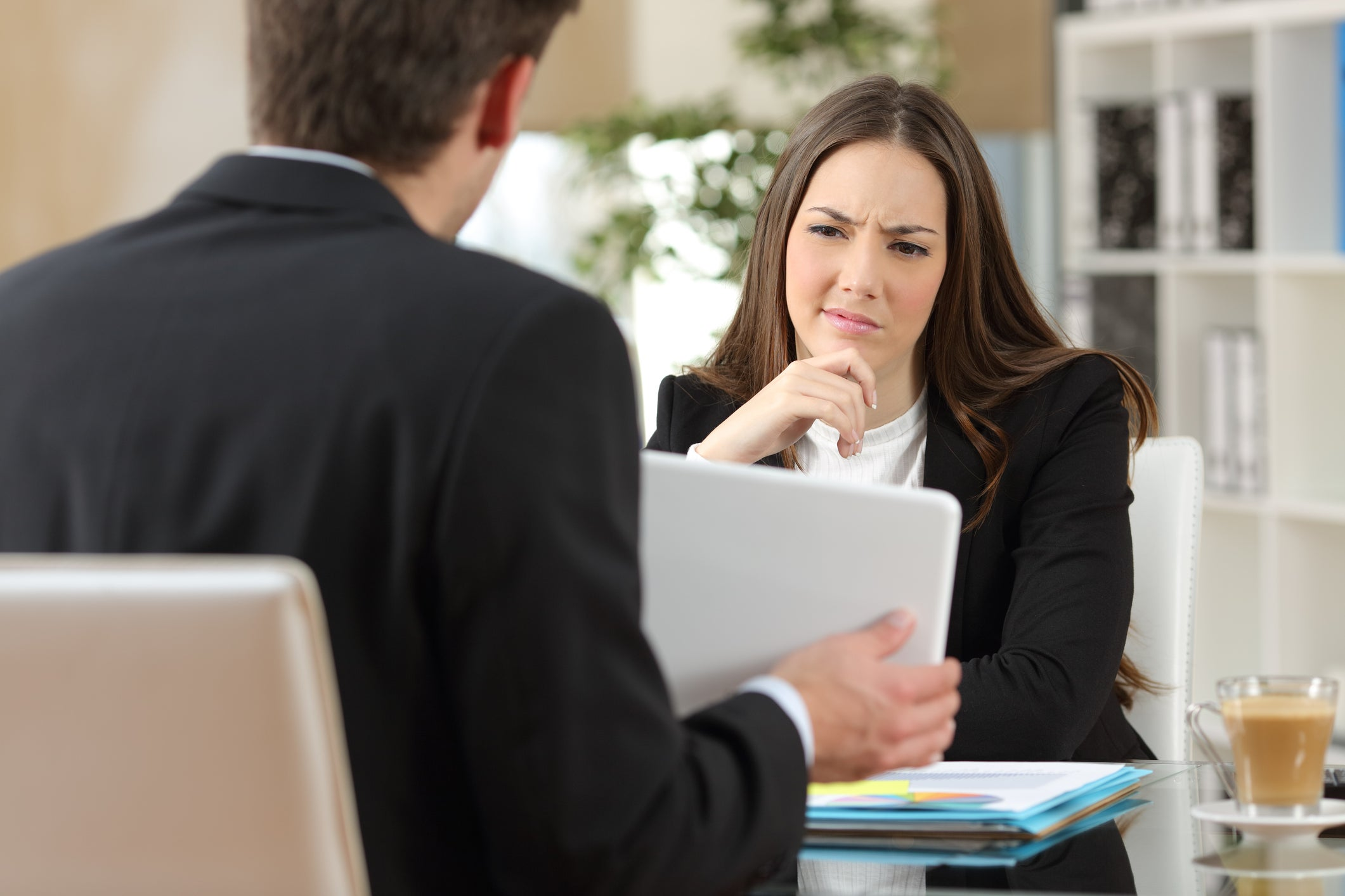 Woman in a suit looking skeptical at a tablet held by a man sitting across from her.