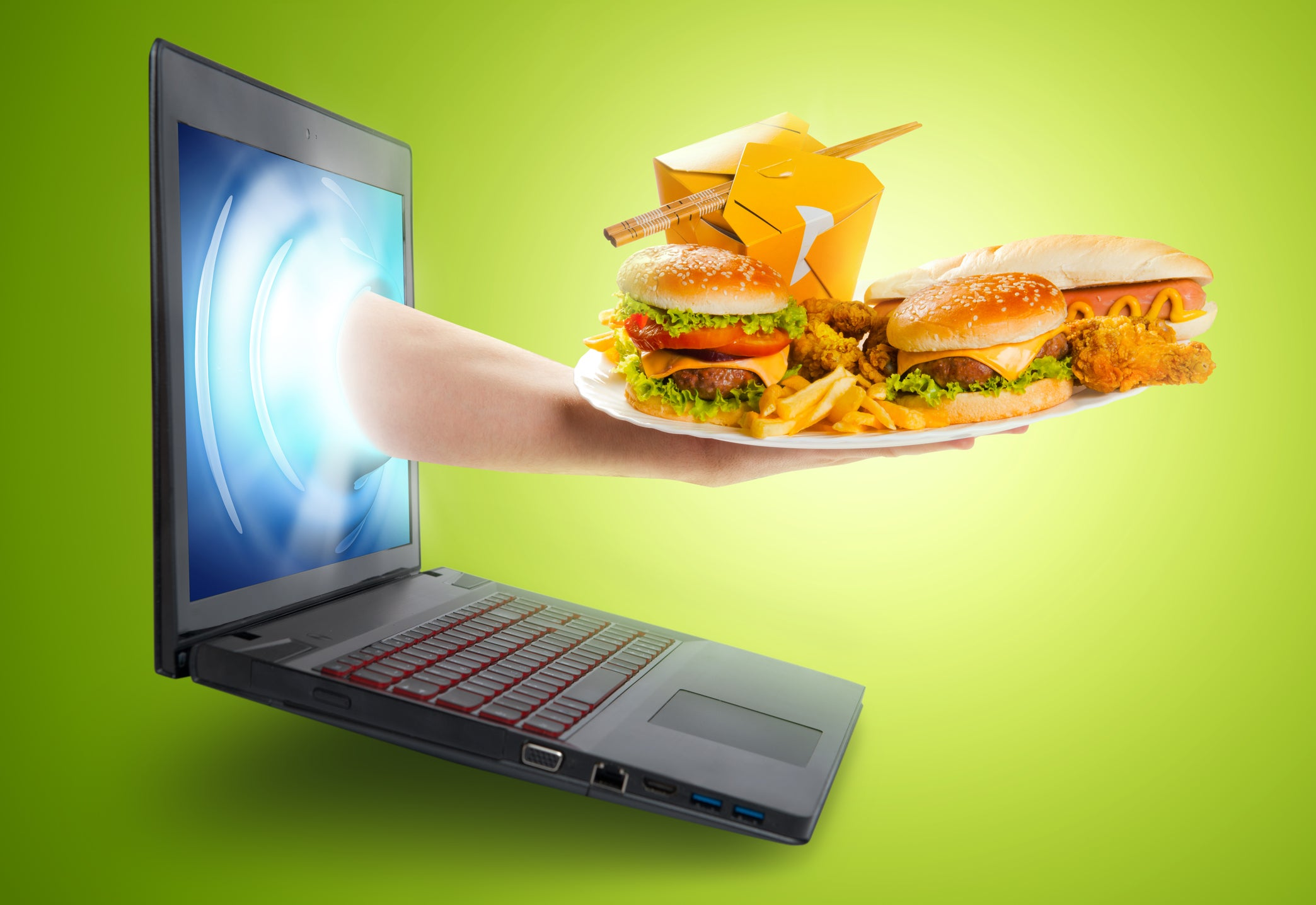 Hand reaching through laptop screen holding plate of fast food