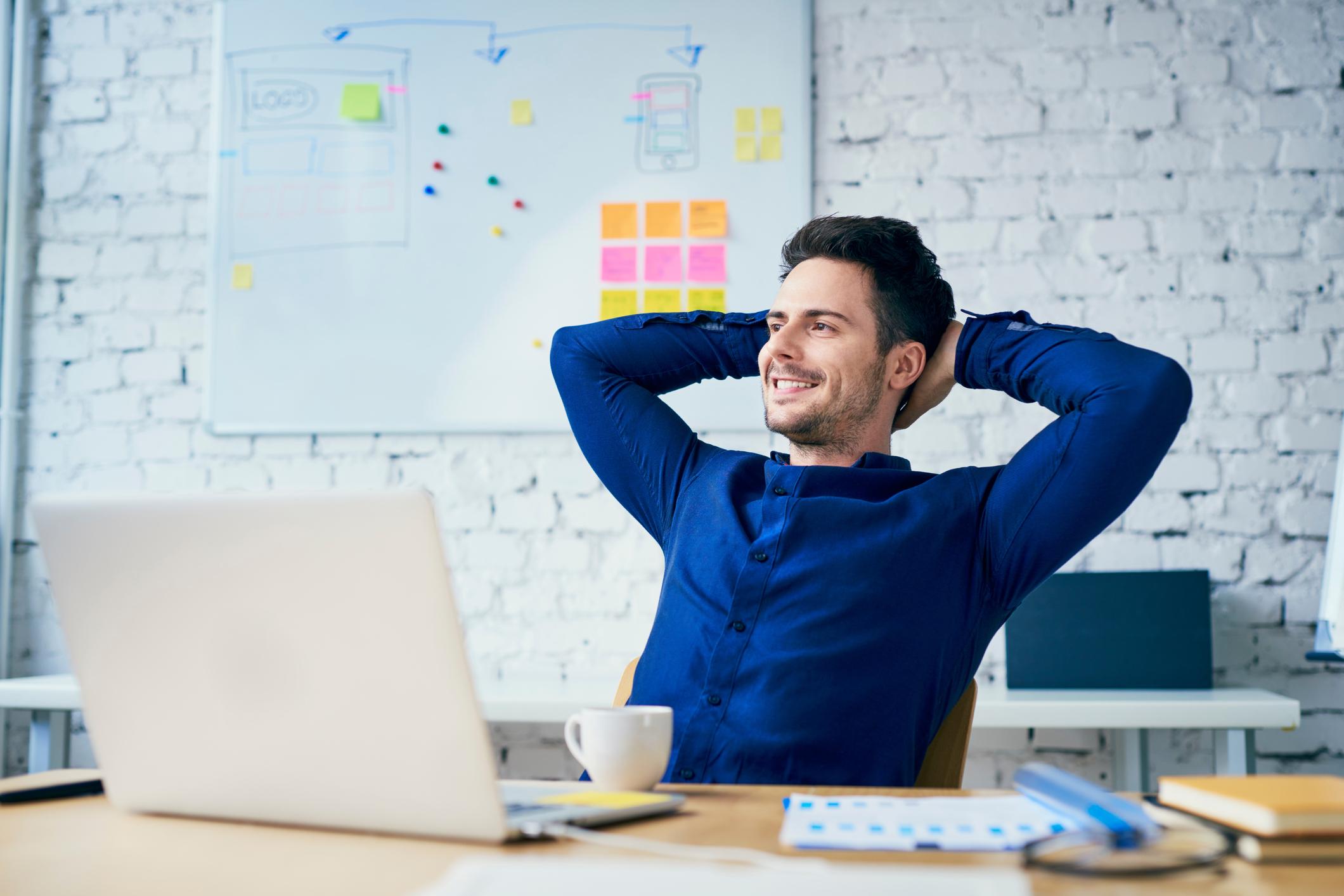 Un homme se recule dans son fauteuil, les mains derrière la tête, souriant. Un ordinateur portable est sur la table devant lui.