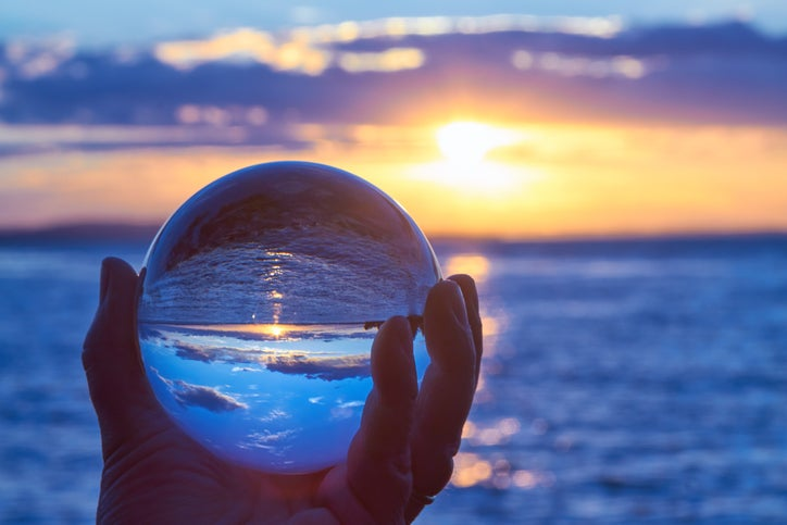 Hand holding a crystal ball in front of a body of water and sunset or sunrise.