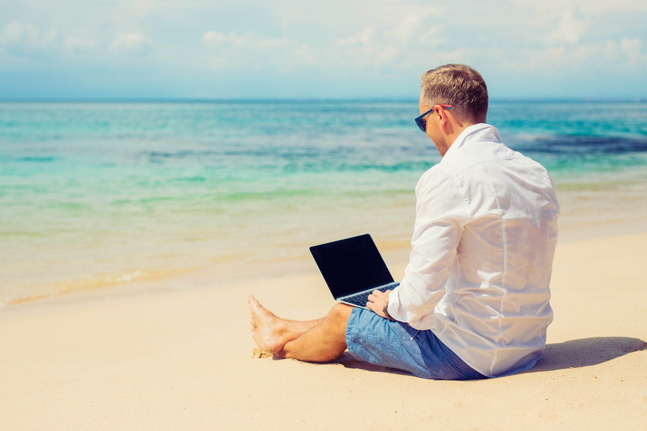 Man typing on laptop while sitting on the beach