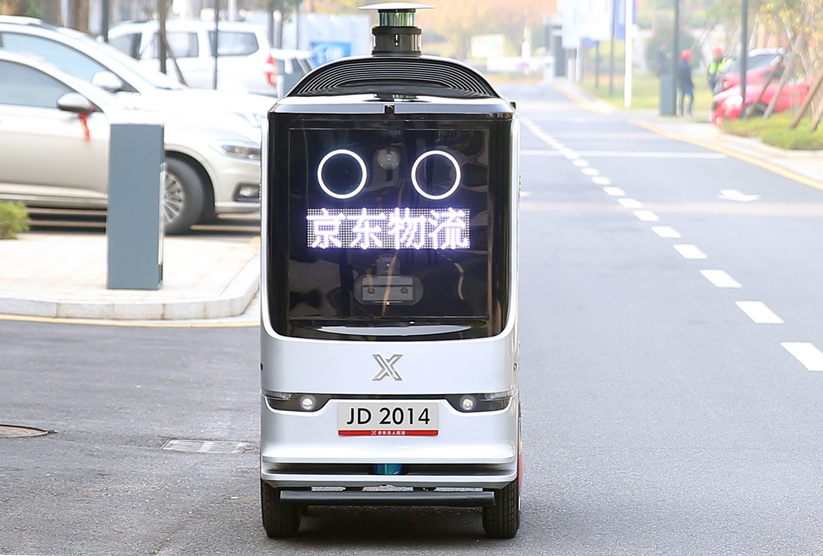 One of JD's autonomous delivery robots is seen on the street.