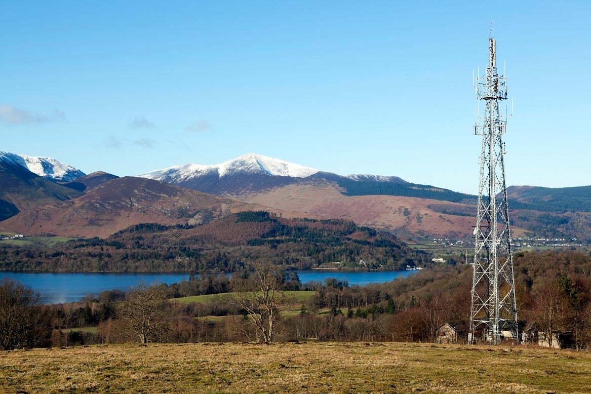 Cell tower in front of a lake and mountains.