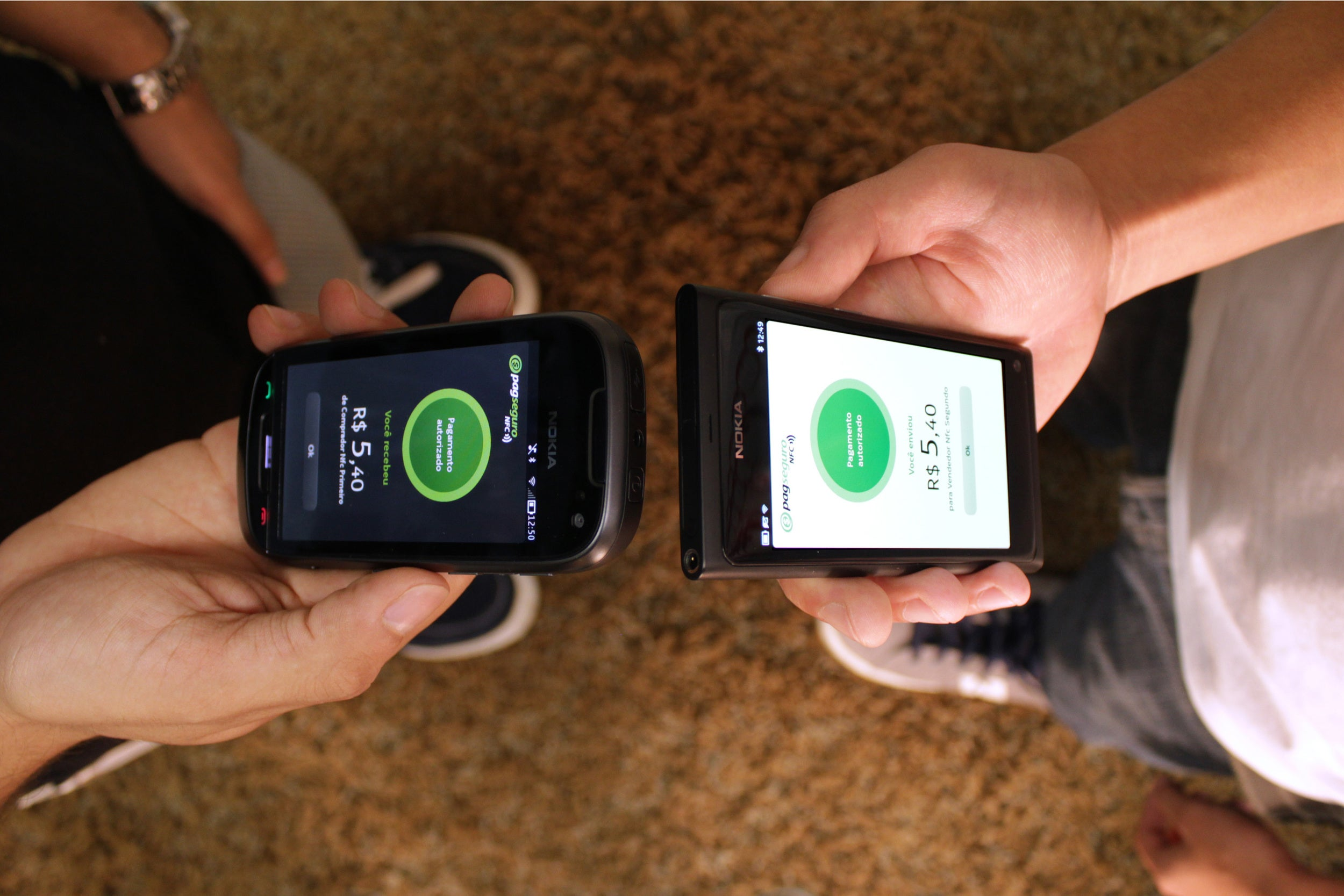 Two people, standing face to face, conducting peer-to-peer payment with their mobile phones.