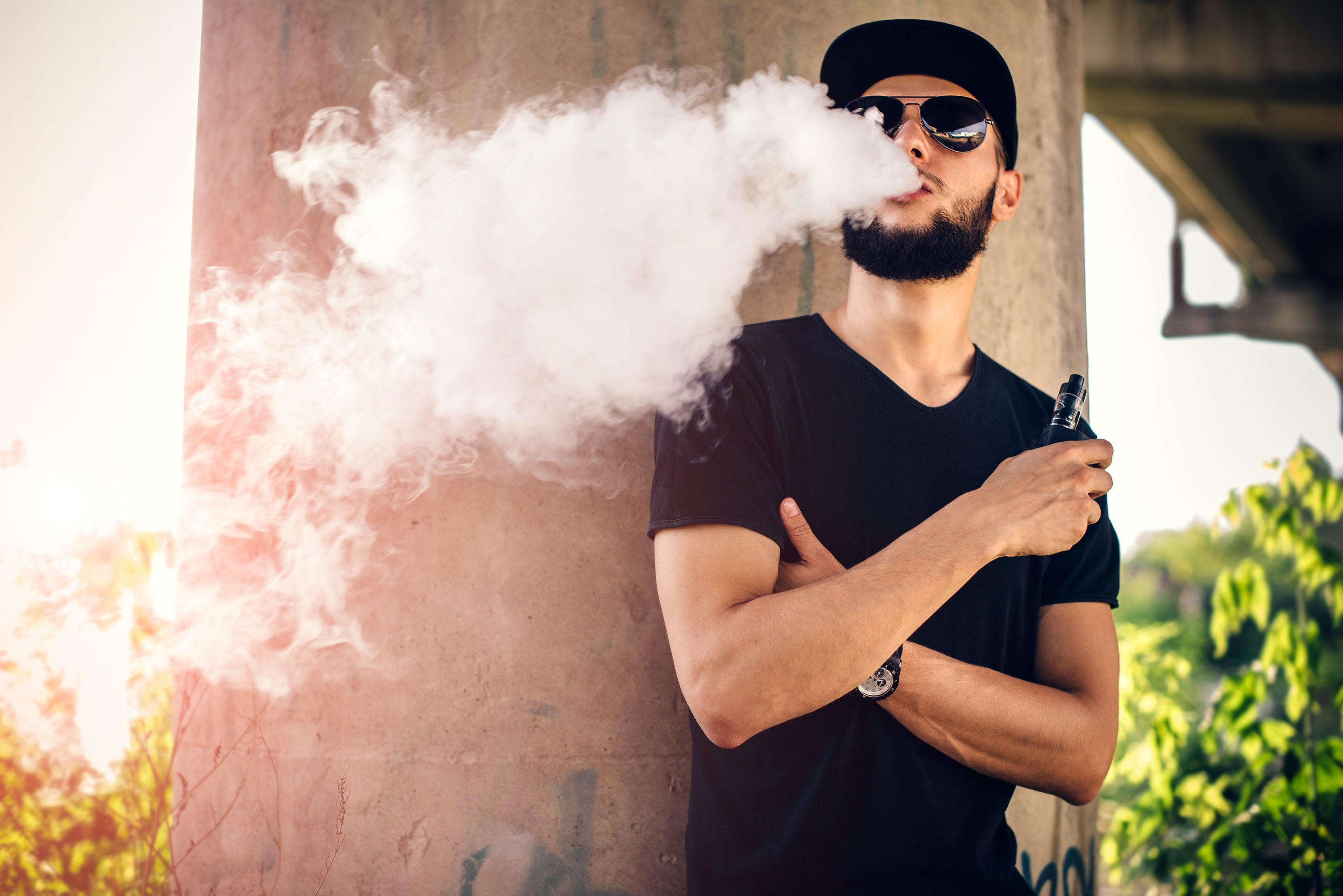 A young man with a beard and sunglasses blowing vape smoke out of his mouth while outside.