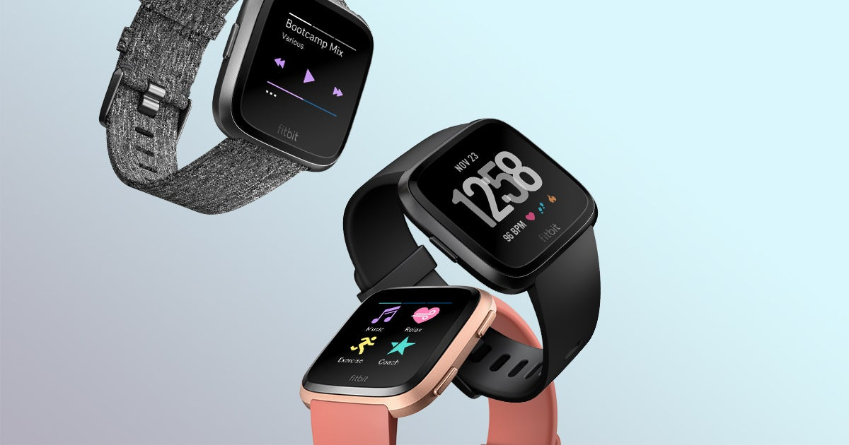 Three Fitbit Versa smartwatches displayed in gray, black, and pink.