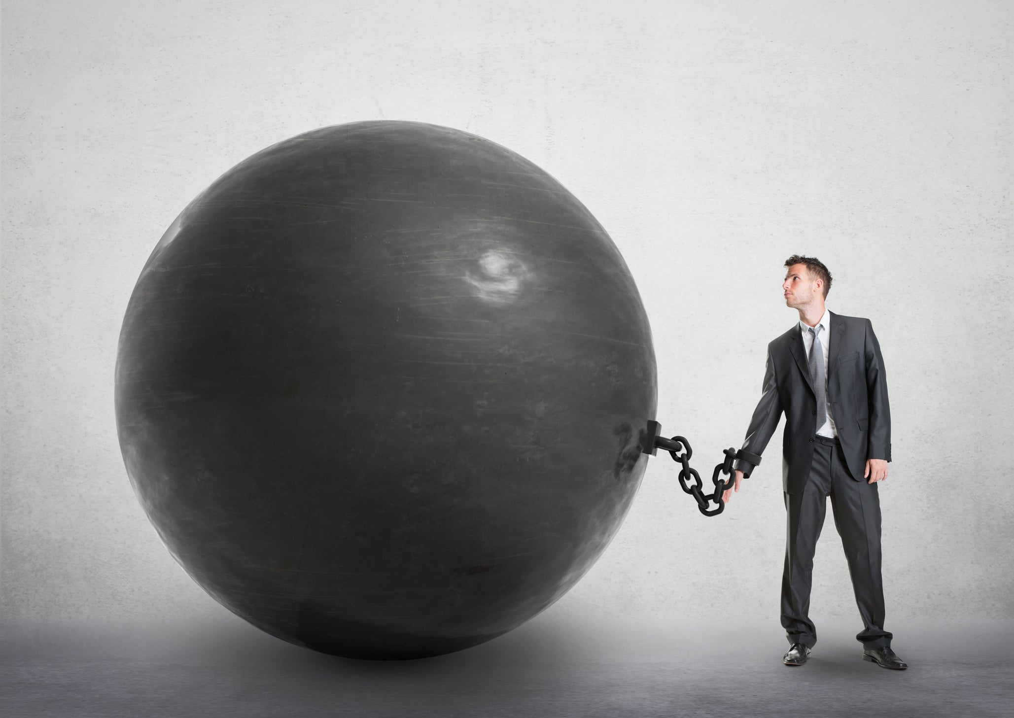 A man in a suit is shackled to a huge black ball that's bigger than he is.