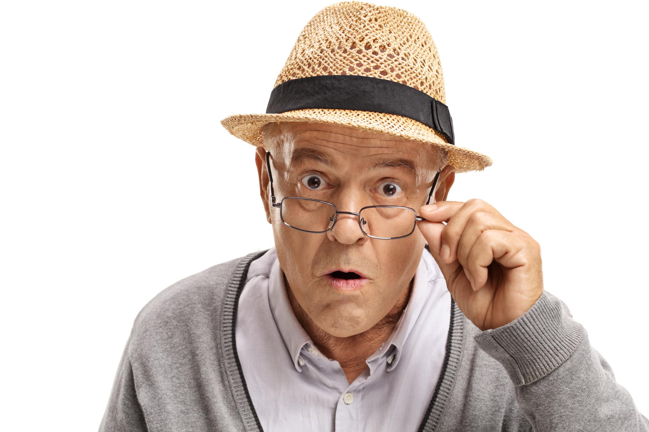 Older man with surprised expression adjusting glasses