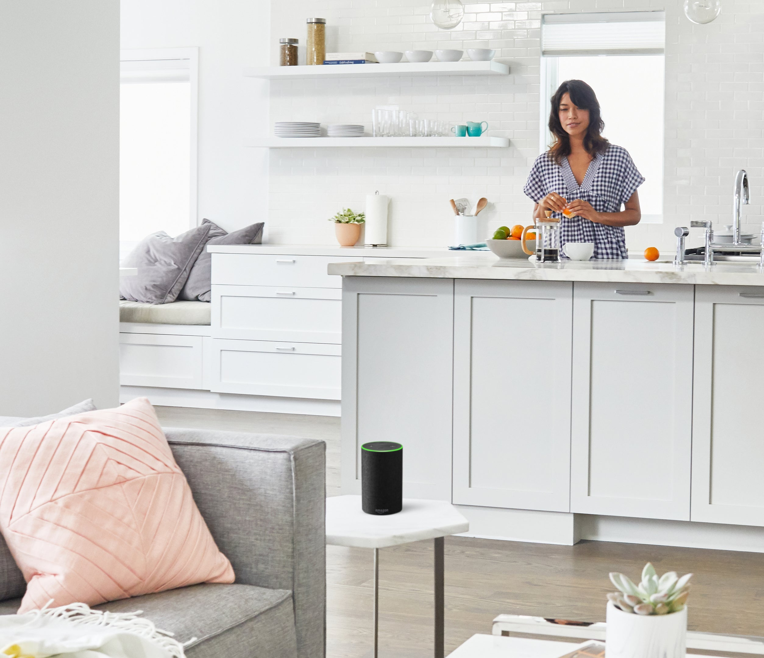 A woman peeling an orange at the kitchen counter, looking at an Echo smart speaker on a small table in the adjacent living room.