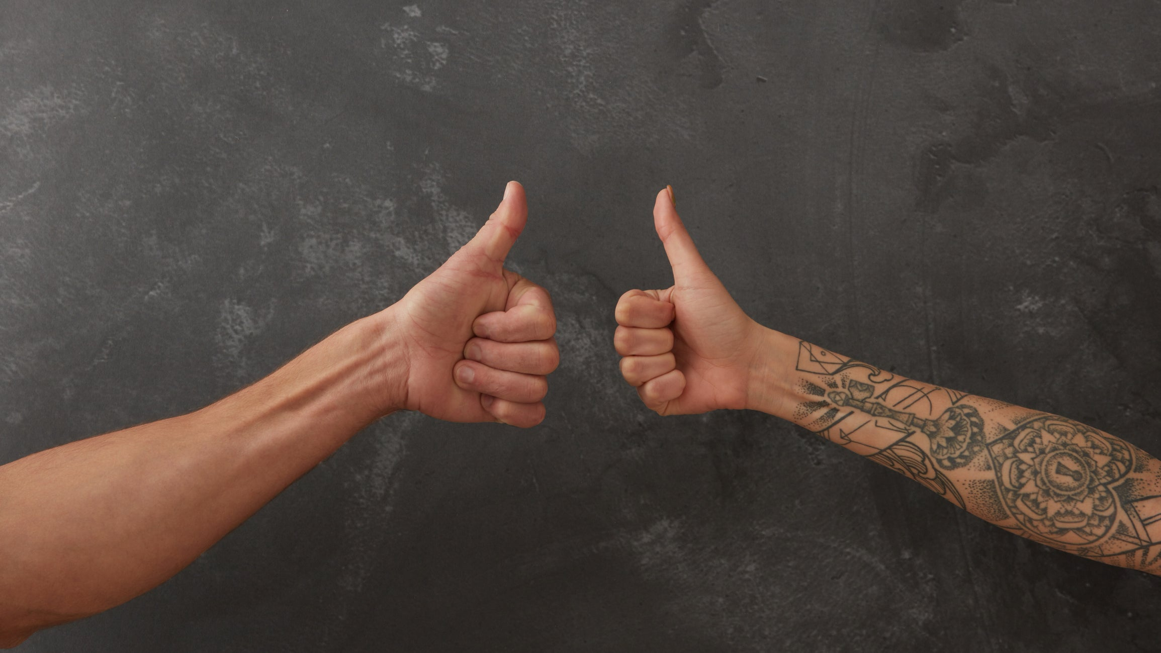 Two thumbs up, one with tattoos on the arm