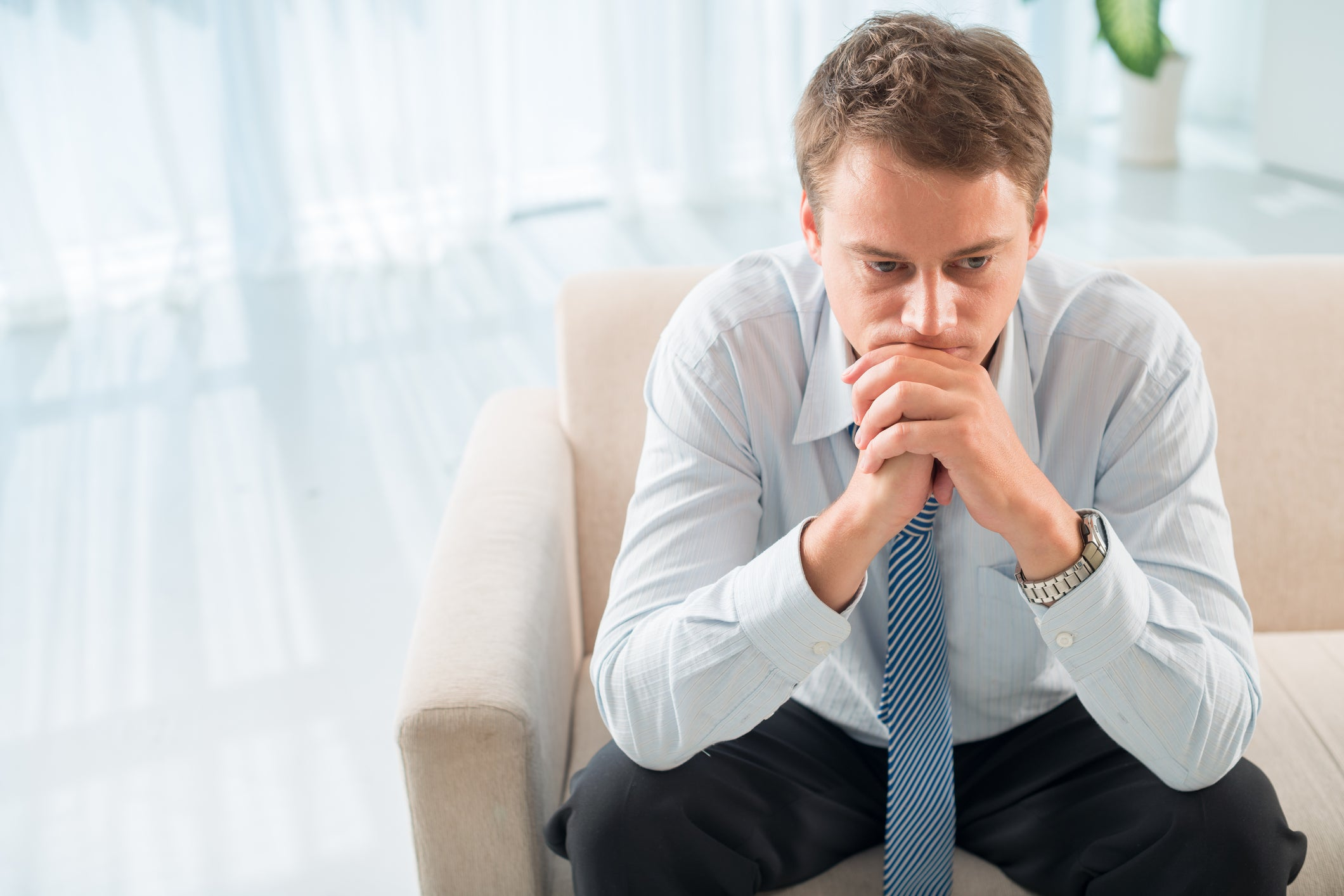 Man in dress shirt and tie sitting on couch, covering his mouth and chin with hands as if worried
