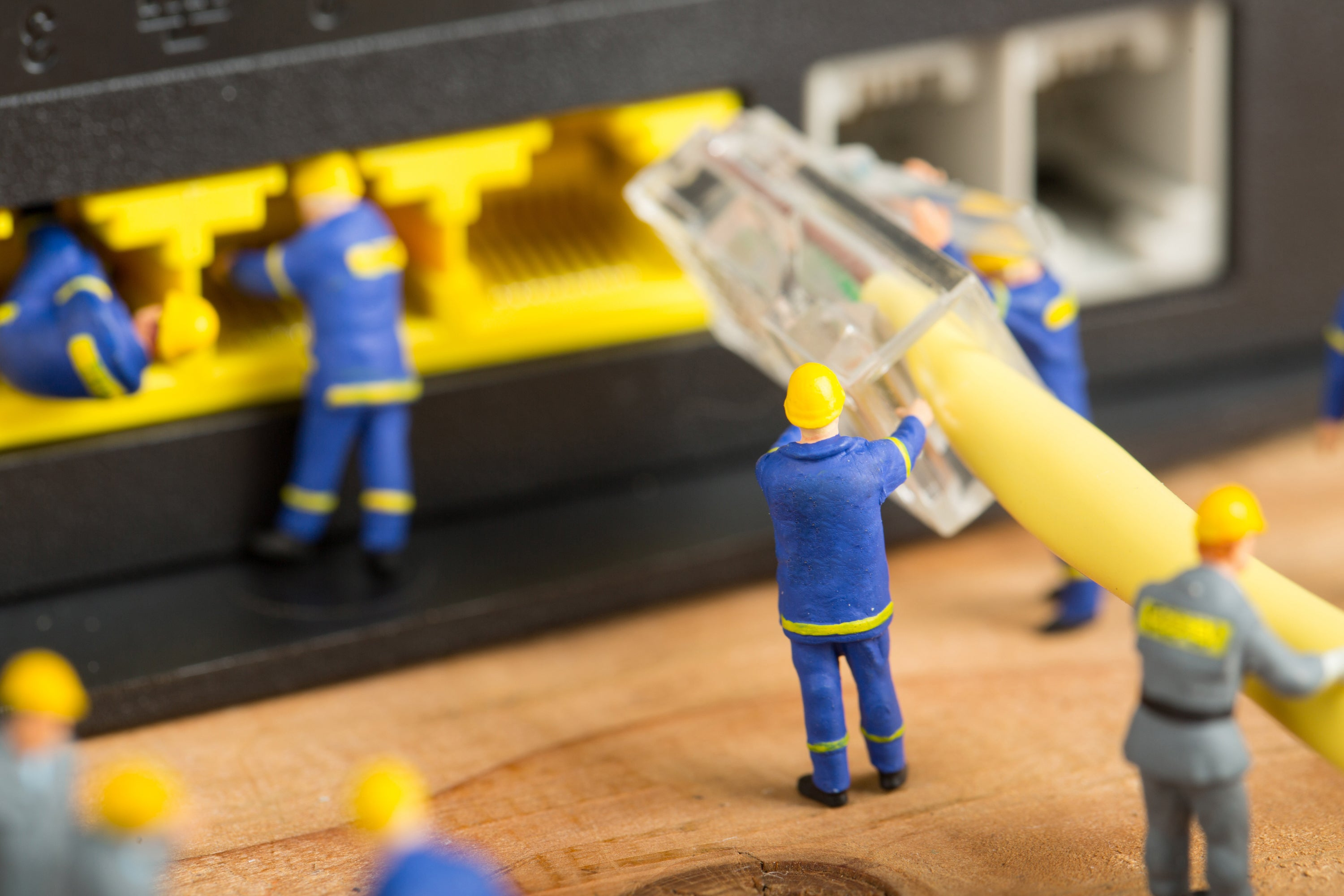 A handful of miniature workers are connecting a huge Ethernet cable to a network port.
