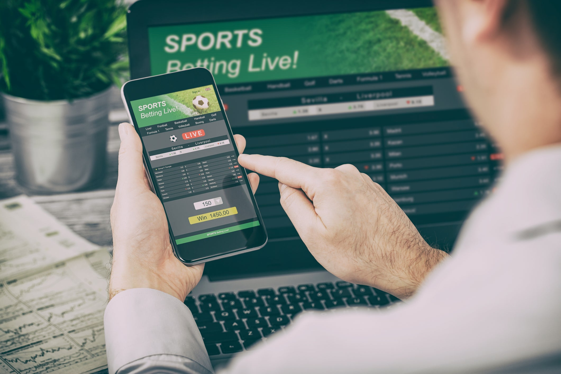 Over the shoulder look at a man pushing buttons on his cell phone with his laptop open in back of it and both on sports betting websites.