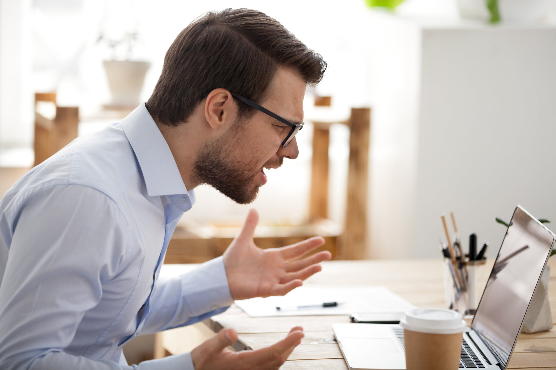 Man looking at laptop computer holding his hands up as if he's frustrated