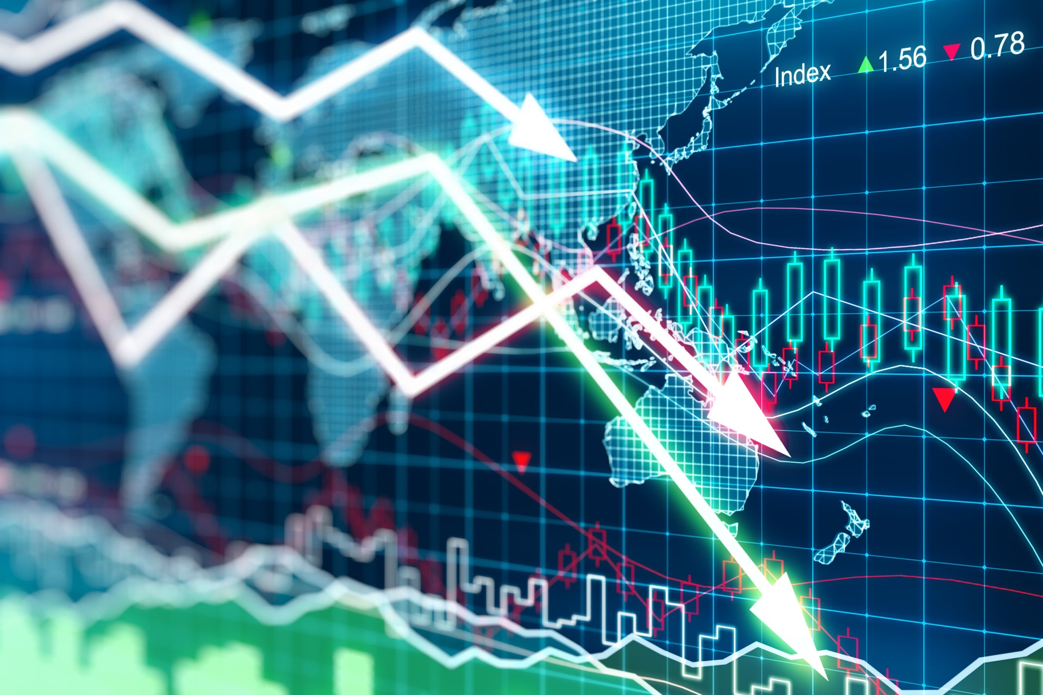 Stock charts trending downward with a map in the background