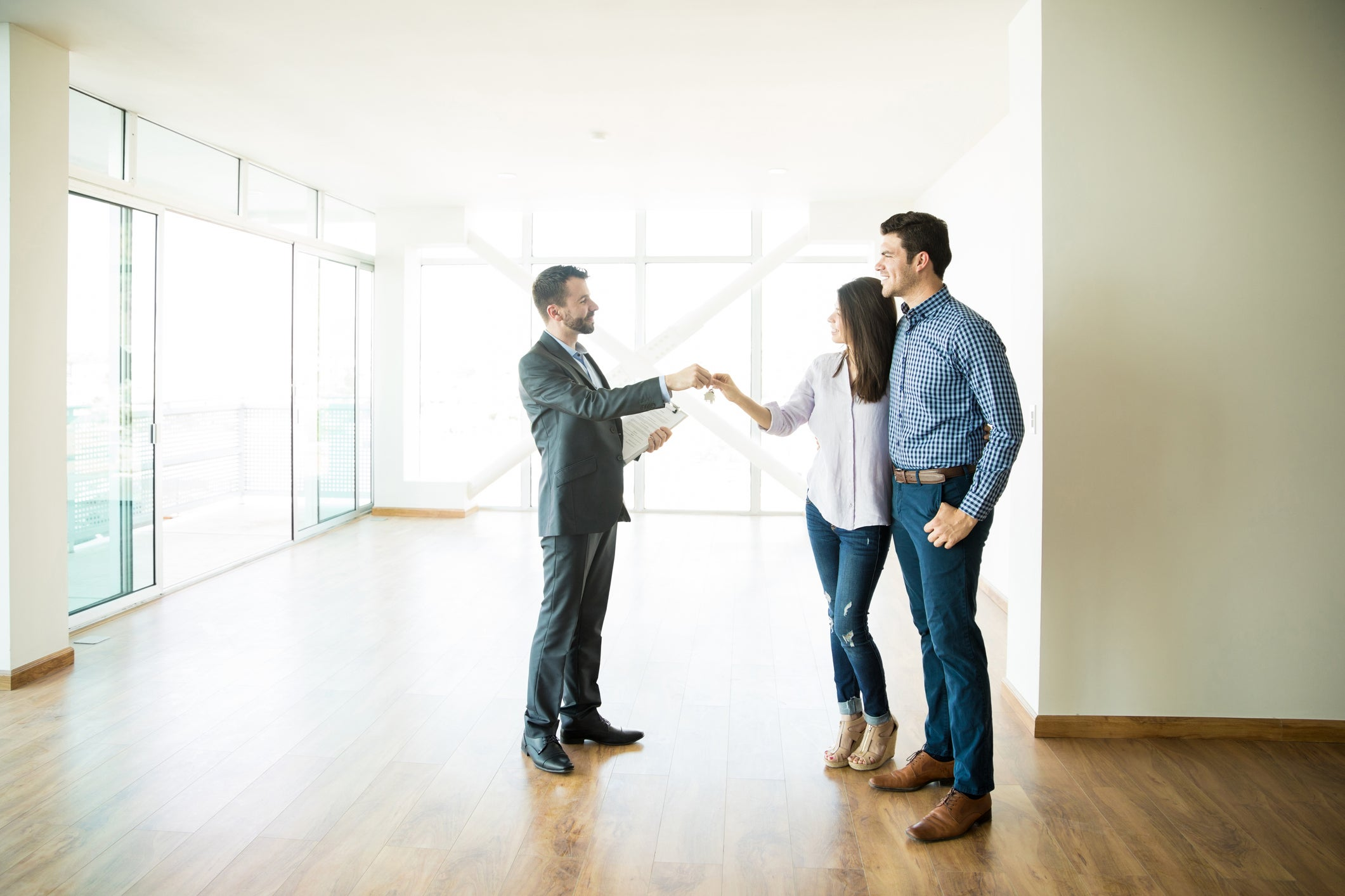 Man and woman in home with no furniture receiving keys from a man dressed in a suit