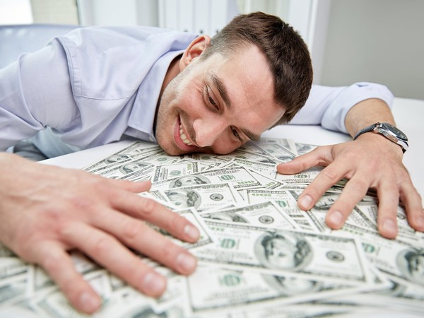 Businessman Admiring Money on Desk Getty