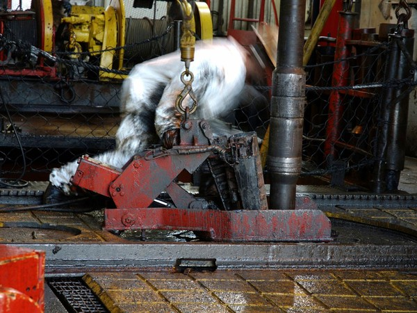 Roughneck setting drill pipe on rig 1200