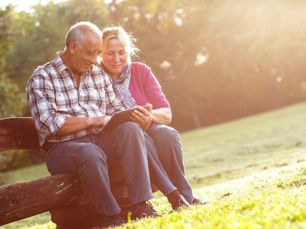 baby boomer couple on a park bench_GettyImages-514000096