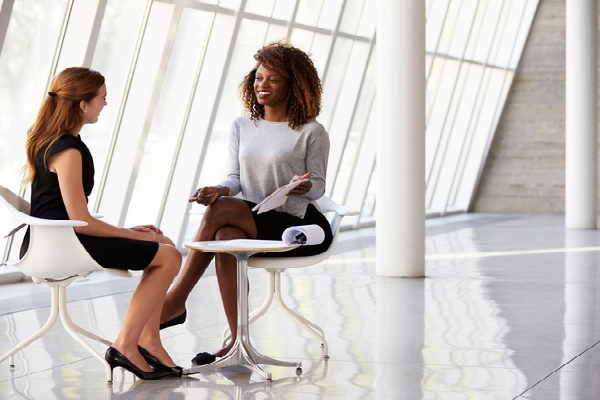 professional women speaking in modern office business meeting mentor