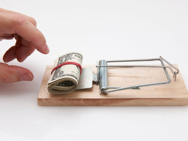 hand reaching towards money on a mouse trap