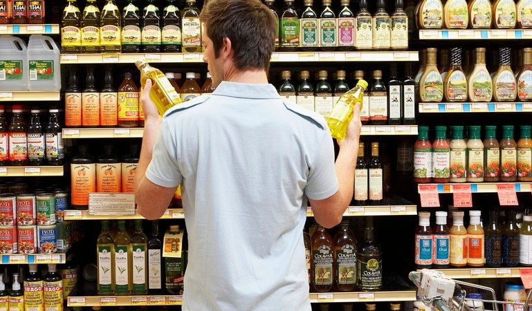 Young man comparing bottles  grocery shopping crop