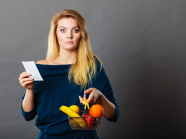 young woman holding produce and receipt upset about cost price sticker shock inflation