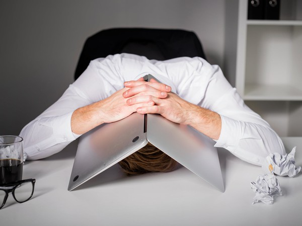 man hiding under laptop_GettyImages-518897996