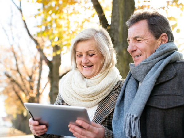 senior couple looking at a tablet outdoors_GettyImages-609033720