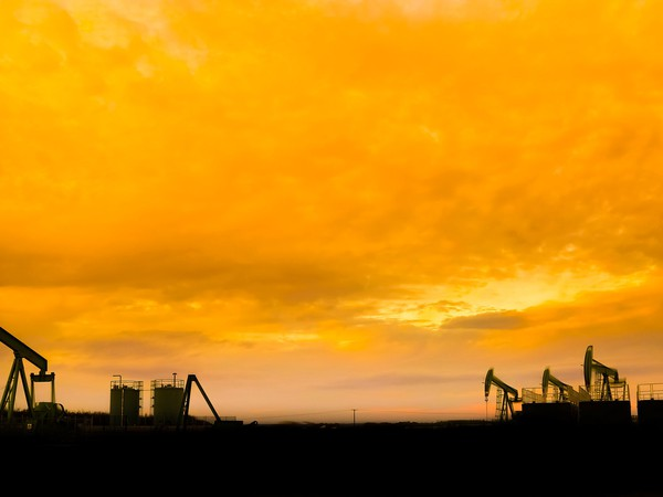 Silhouette of Oil pumps at oil field with nice sunset sky background.