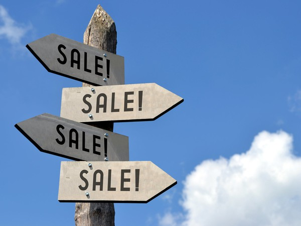 Wooden signpost with 4 sale signs