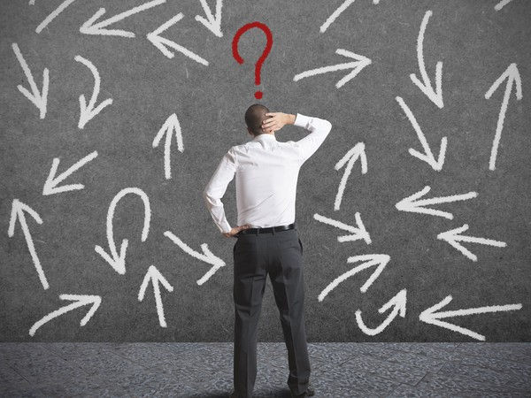 man standing in front of a wall full of question marks