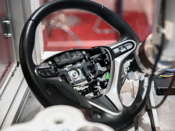 A robotic arm builing a car steering wheel.