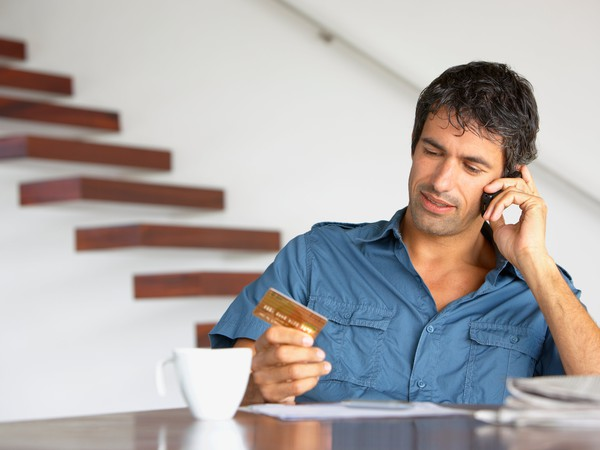 man with credit card on phone