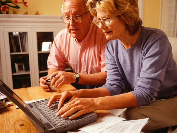senior couple using laptop and credit cards