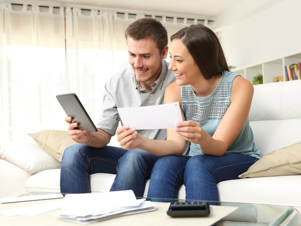 couple happy with bills_GettyImages-623211758