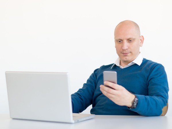 man checking phone while working on laptop_GettyImages-504869430