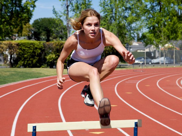 Female Leaping Over Hurdle On Circular Track