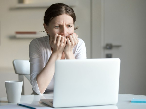 worried woman looking at laptop computer