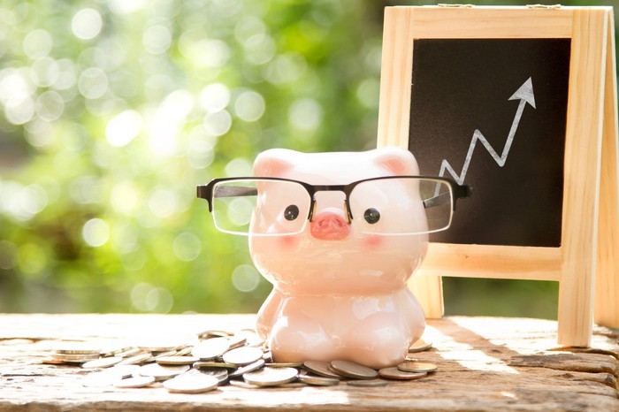 Piggy bank wearing glasses sitting on a pile of coins, with a blackboard in the background