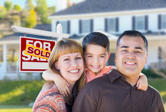 Smiling man, woman, and child in front of house with sold sign