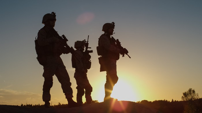 Three soldiers in silhouette.