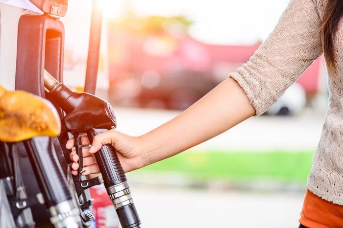 Woman holding gas pump