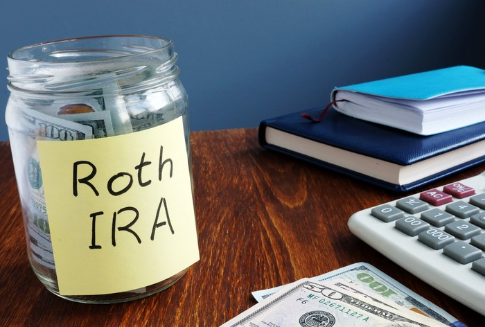 """""""Roth IRA"""" written on a Post-it on a jar containing money."""