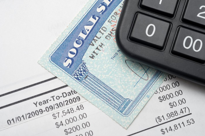 A black calculator on top of a Social Security card and an income statement.