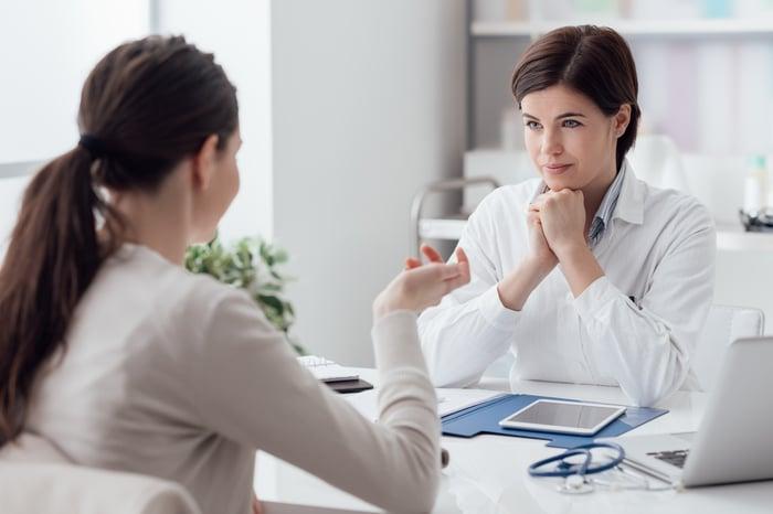 Two women conversing across a desk in an apparent medical setting